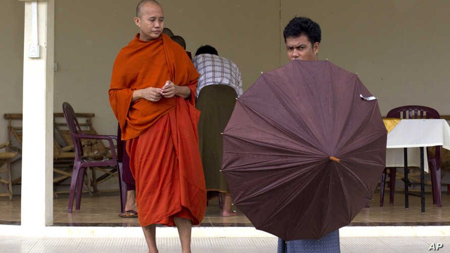 A Buddhist devotee holds an umbrella ready to shelter controversial Buddhist monk Wirathu (L), who is accused of instigating sectarian violence between Buddhists and Muslims through his sermons, after an assembly of Burma's powerful Buddhist clergy,