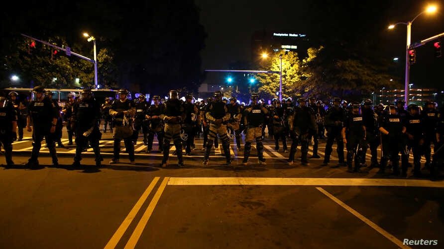 Police in riot gear block a roadway to stop demonstrators from entering a neighborhood as they protest the police shooting of Keith Scott in Charlotte, North Carolina, U.S., September 25, 2016.