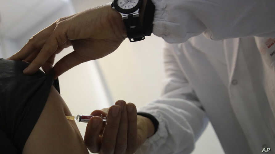 FILE - A doctor injects vaccine into a patient's arm, in Rome, Italy, Feb. 23, 2018.