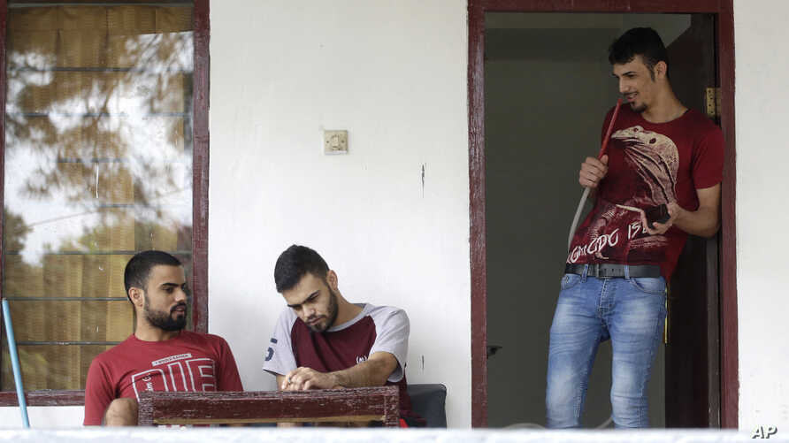FILE -  Iraqi asylum seeker Ayman, right, chats with his brother, left, and friend, center, during an interview with The Associated Press at temporary home in Puncak, West Java, Indonesia, Jan. 31, 2017.