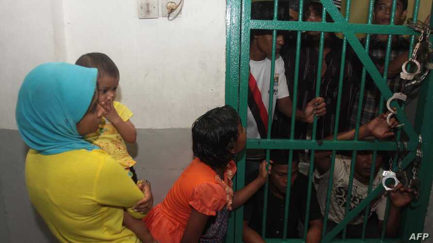 A woman and her children visit their husband and dad of Myanmar Rohingya Muslims at the court's detention house in Medan, North Sumatra, Dec. 4, 2013, before the verdict.
