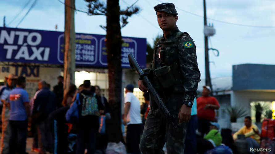 An army soldier patrols on a street next to people from Venezuela after checking their passports or identity cards at the Pacaraima border control, Roraima state, Brazil, Aug. 19, 2018.