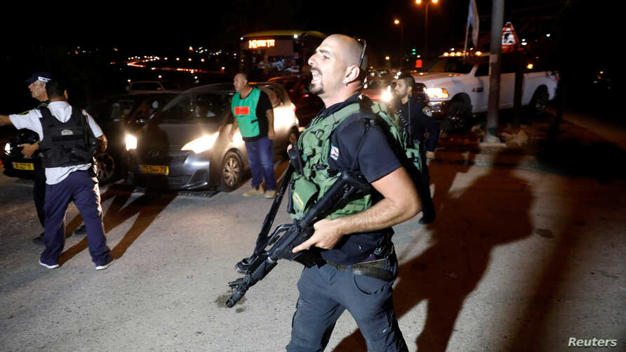 A security guard walks into the Israeli settlement Adam after a Palestinian assailant stabbed three people and then was shot and killed, according to the Israeli military, in the occupied West Bank, July 26, 2018.