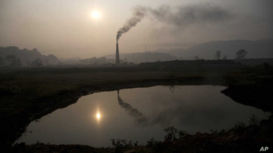Smoke rises from a brick kiln on the outskirts of Gauhati, India, Monday, Jan. 26, 2015. The World Meteorological Organization reports greenhouse gas concentrations in the atmosphere last year hit a new high and 2015 looks as though it will be anothe