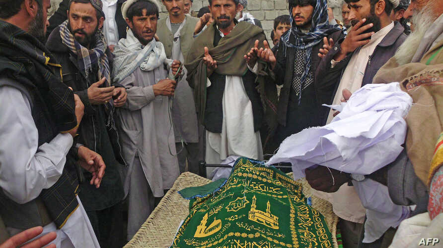 Afghan men pray during the funeral of Nadia Sidiqi, the acting director of the women's affairs department in Mihtarlam, December 10, 2012.