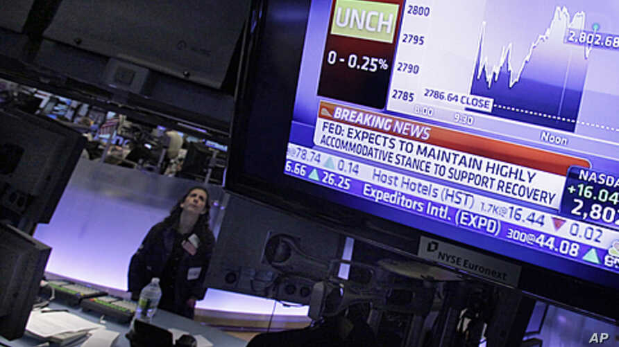 Specialist Tina Vlitas watches the rate decision of the Federal Reserve as she works on the floor of the New York Stock Exchange, January 25, 2012.