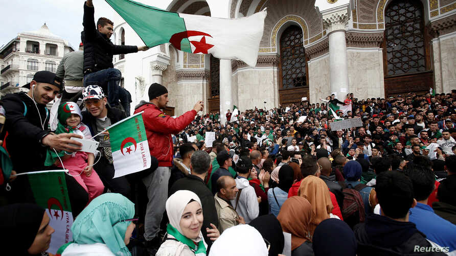 FILE - People carry national flags and banners during a protest calling on President Abdelaziz Bouteflika to quit, in Algiers, Algeria, March 26, 2019.