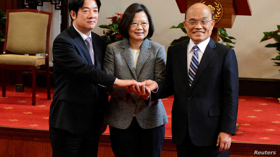 Former premier William Lai, left, Taiwan President Tsai Ing-wen and new premier Su Tseng-chang, right, join hands after a news conference in Taipei, Taiwan, Jan. 11, 2019.
