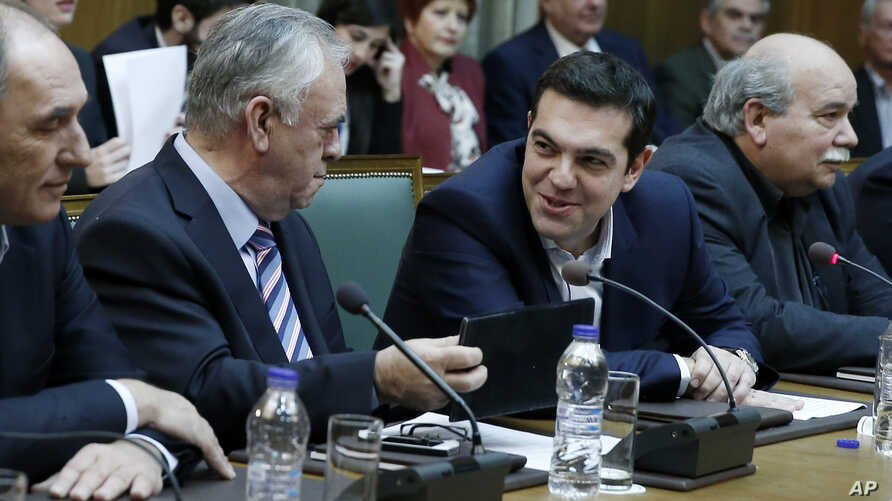 Greece's Prime Minister Alexis Tsipras, second right, and Deputy Prime Minister Giannis Dragasakis, second left, chat during the first cabinet meeting of the new government at the Parliament in Athens, on Wednesday, Jan. 28, 2015.