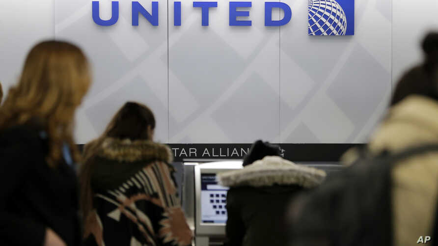 FILE-  People stand in line at a United Airlines counter at LaGuardia Airport in New York, March 15, 2017. A dog died on a United Airlines flight from Houston to New York after a flight attendant ordered its owner to put the animal in the plane's ove