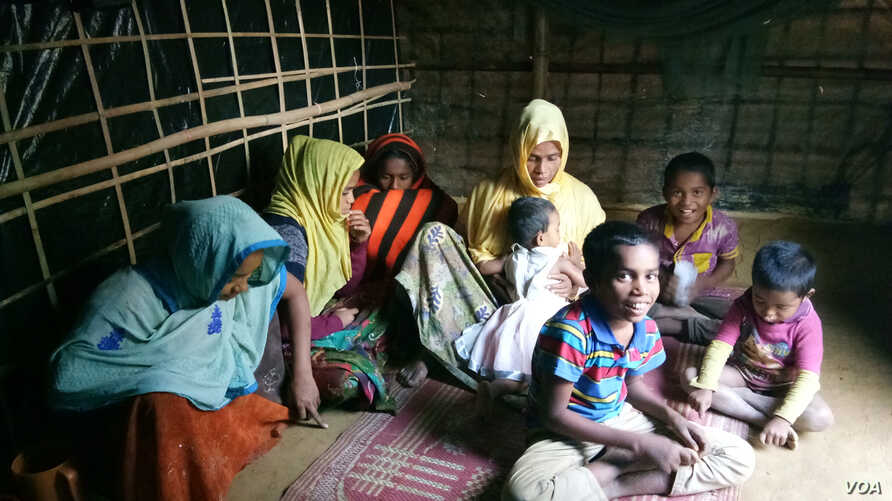 Samsun Nahar, a Rohingya widow, along with her 9 children at her bamboo-and-plastic shack in a refugee colony in Kutupalong, Cox's Bazar, Bangladesh. Nahar is looking for grooms for her daughters, ages 13 and 14. (Photos by Noor Hossain)
