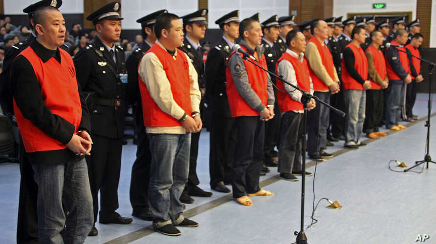 In this photo taken Oct. 12, 2009, Yang Tianqing, first left, and other unidentified suspects allegedly ivolved in mafia-style gangs stand trial at the Chongqing No.1 Intermediate People's Court in Chongqing, China.