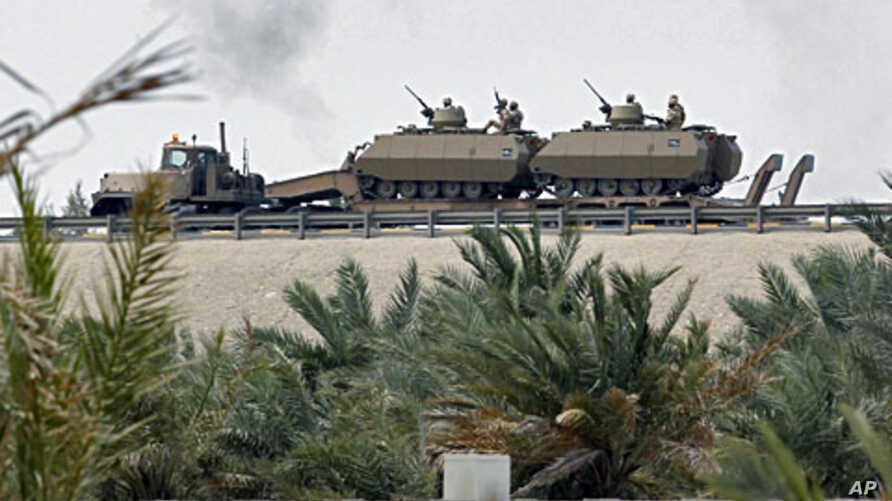 Armored personnel carriers are transported on the flyover near the Bahrain Saudi bridge in Manama Mar 15 2011