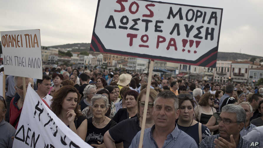 """Protesters hold a placard which reads in Greek """"SOS Moria. Solution now"""" referring to the Moria refugee camp, during a protest in the town of Mytilene on the northeastern Aegean island of Lesbos, May 3, 2018."""