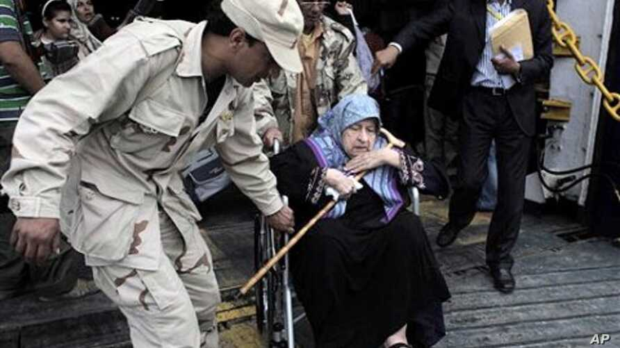 A rebel helps an elderly evacuee Libyan woman on a wheelchair disembarking the Albanian ferry Red Star 1 that evacuated injured people and refugees fleeing the battered city of Misrata, after docking at the port of Benghazi, Libya, April 28, 2011