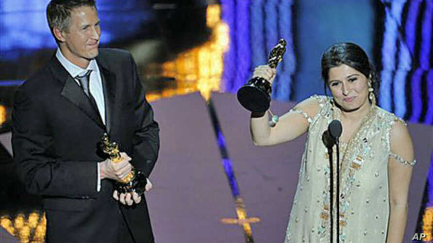Daniel Junge (L) and Sharmeen Obaid-Chinoy accept the Oscar for best documentary short for 'Saving Face' during the 84th Academy Awards in the Hollywood section of Los Angeles, February 26, 2012.