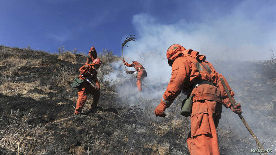 FILE - Forest policemen put out the remains of a fire at a mountainous Tibetan region in Daofu county, Sichuan Province. Dec. 6, 2010. (Reuters/China Daily)