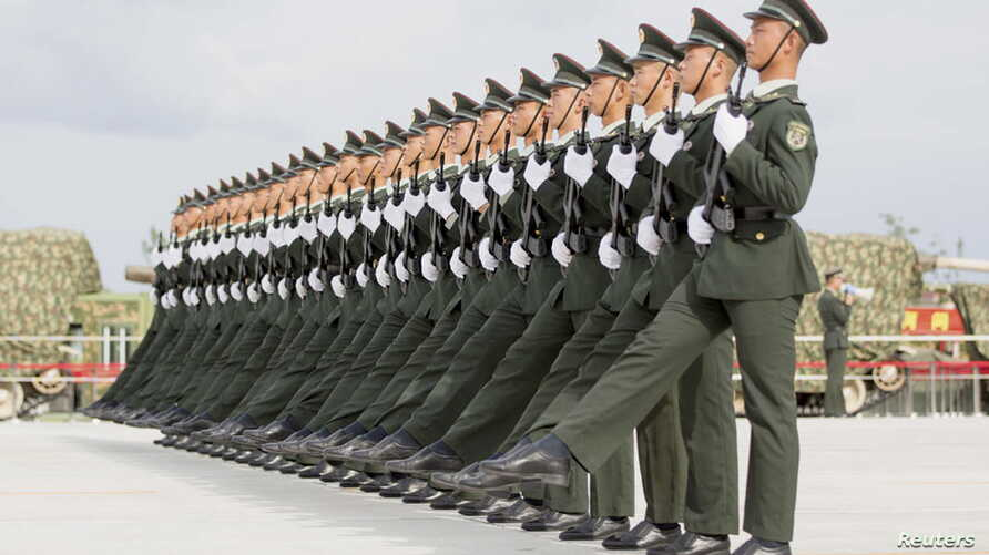 Soldiers of China's People's Liberation Army march with their weapons during a training session for a military parade to mark the 70th anniversary of the end of World War II, at a military base in Beijing, Sept. 1, 2015.