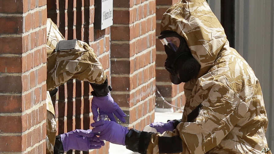 Specialist team members in military protective suits use a jar in the front doorway as they search the fenced off John Baker House for homeless people on Rollestone Street in Salisbury, England, July 6, 2018.
