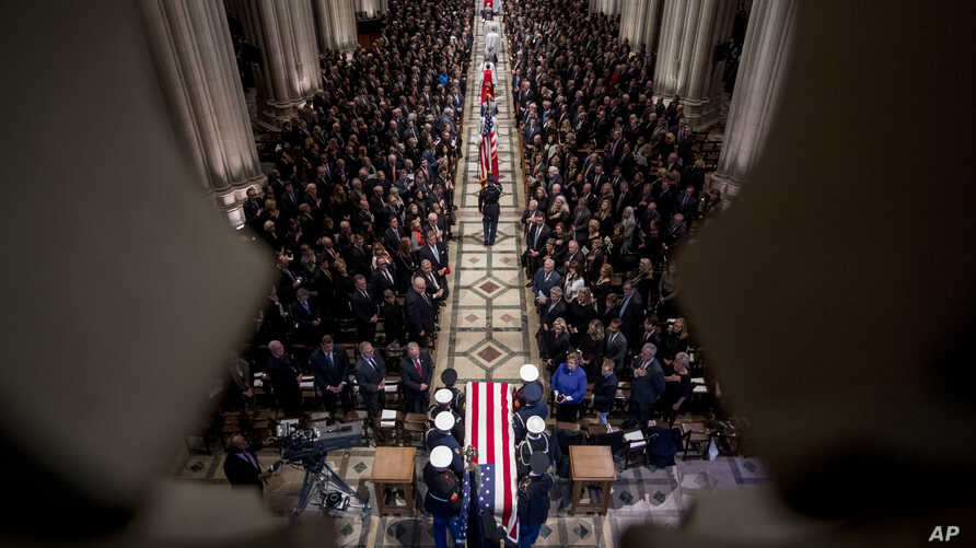 The flag-draped casket of former President George H.W. Bush is carried by a military honor guard during a State Funeral at the National Cathedral, Dec. 5, 2018, in Washington.