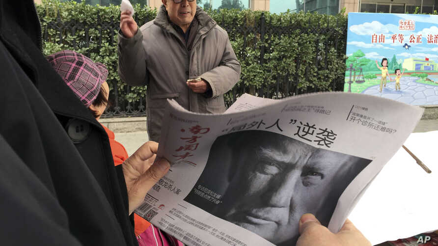 """FILE - A Chinese man holds up a Chinese newspaper with the front-page photo of Donald Trump and the headline """"Outsider counter attack"""" at a newsstand in Beijing, China, Nov. 10, 2016. China has pledged to """"firmly defend its legitimate rights and inte..."""