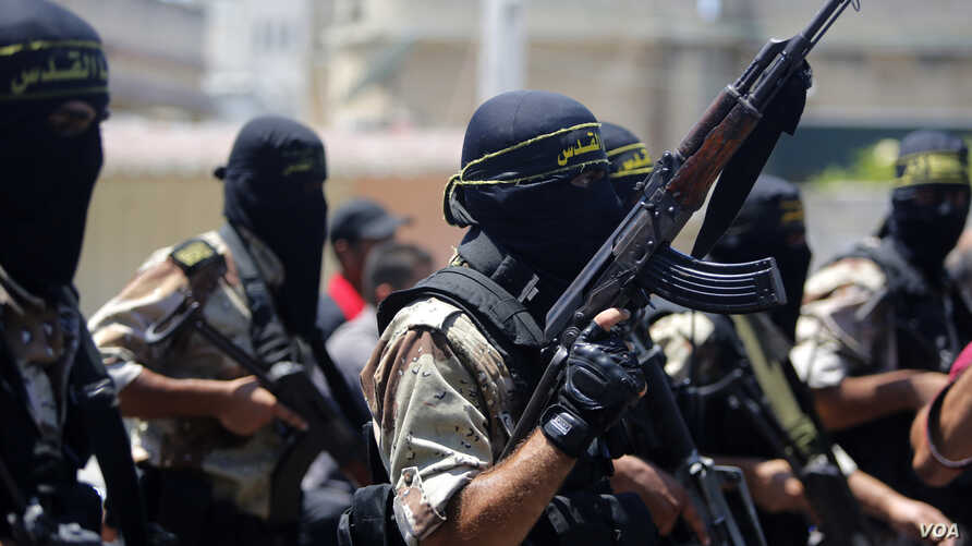 Masked militants of the Islamic Jihad group march during the funeral of their comrade Shaaban Al-Dahdouh, whose body was found under the rubble Tuesday, in Gaza City on Wednesday, Aug. 6, 2014. (AP Photo/Hatem Moussa)
