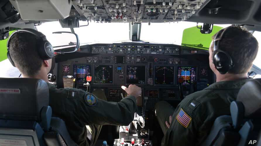 FILE - Lt. j.g. Kyle Atakturk, left, and Lt. j.g. Nicholas Horton, pilot a U.S. Navy P-8A Poseidon during a mission to assist in search and rescue operations for Malaysia Airlines flight MH370 Wednesday March 19, 2014.