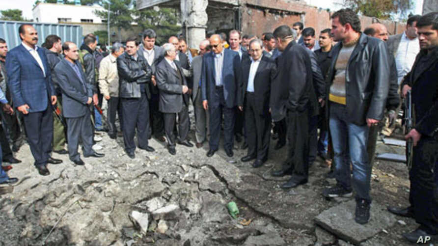 A delegation of Arab League officials visits a site to inspect damages to buildings after a car bomb attack in Damascus, Syria, December 23, 2011.