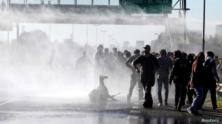 Protestors are sprayed with water by Argentine police as they block a road during a 24-hour national strike in Buenos Aires, Argentina, April 6, 2017.