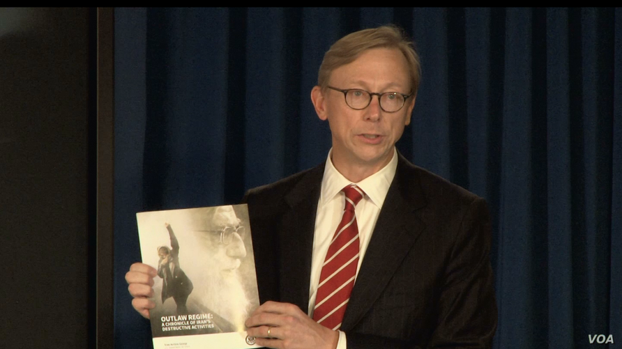 """U.S. Special Representative for Iran Brian Hook speaks at a Sept. 28, 2018, press briefing in New York, holding a copy of the State Department's Sept. 25 report """"Outlaw Regime: A Chronicle of Iran's Destructive Activities."""""""