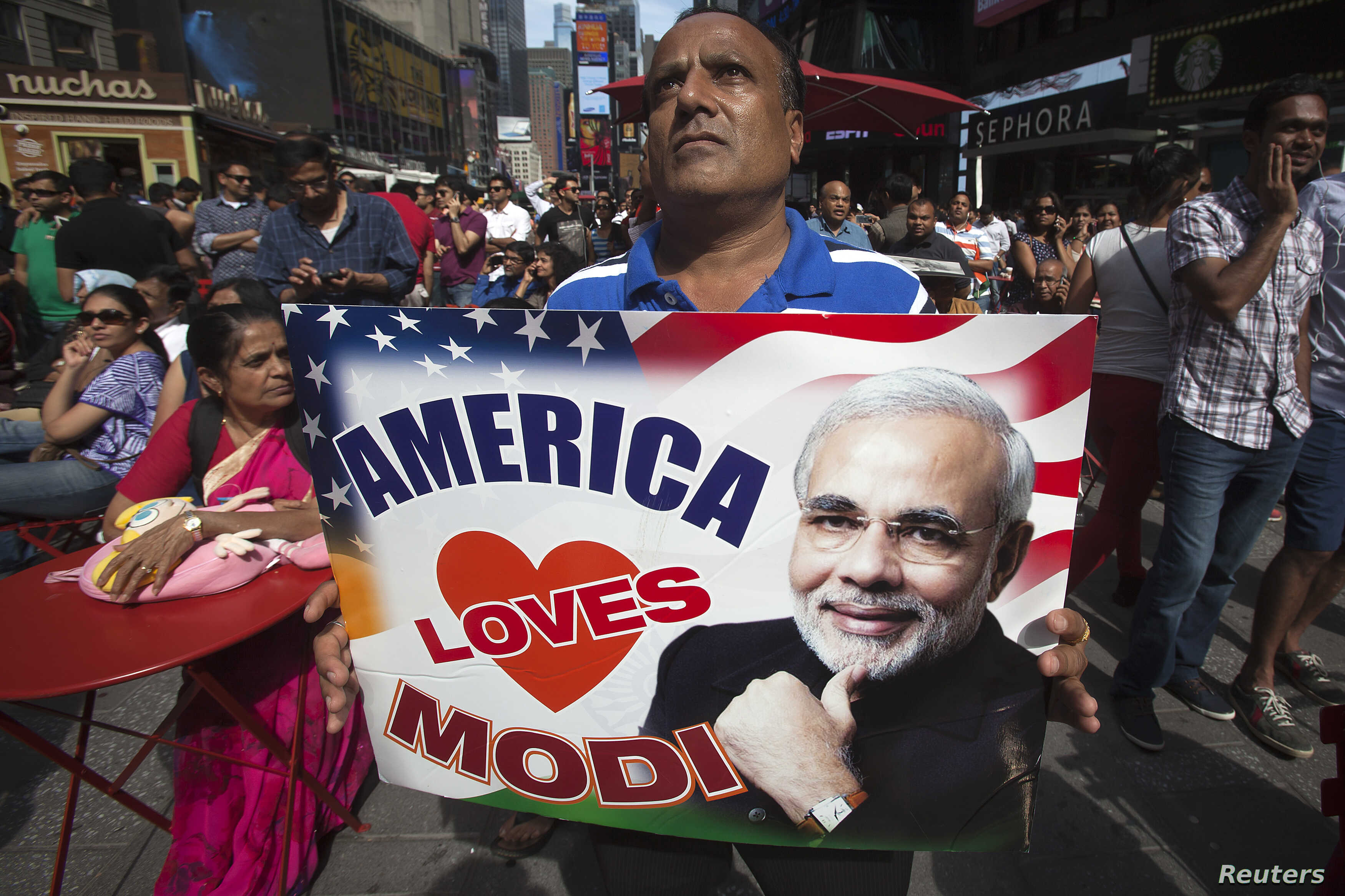 A supporter hold up an America Love Modi sign as he assembles with a large crowd of people in Times Square to watch the speech by India's Prime Minister Narendra Modi simulcast on a giant screen in New York September 28, 2014.    REUTERS/Carlo Allegr