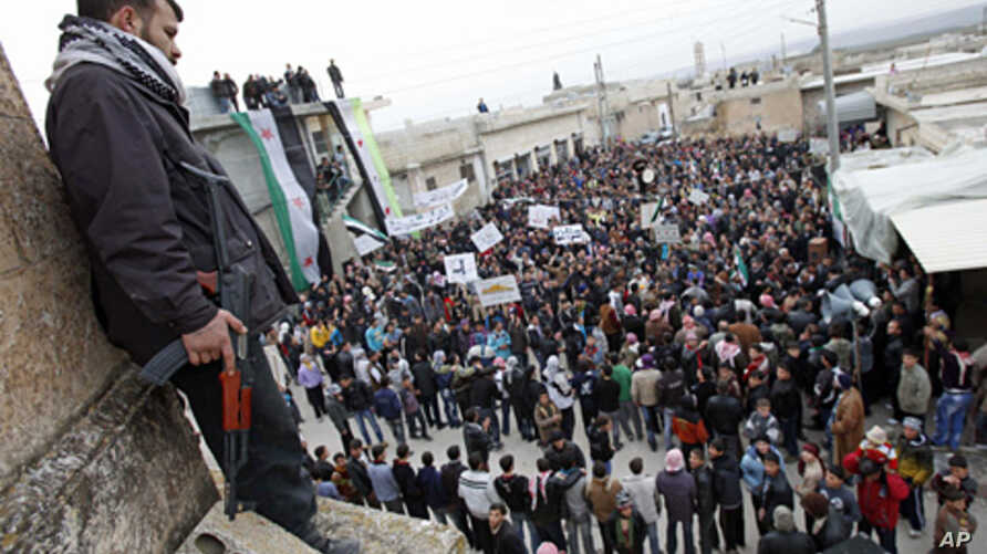 A member of the Free Syrian Army stands guard as anti-Syrian regime protesters hold a demonstration in Idlib, Syria, Feb. 6, 2012.