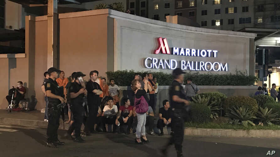 Armed security officers and onlookers gather outside a hotel at the Resorts World Manila complex, early Friday, June 2, 2017, in Manila, Philippines.