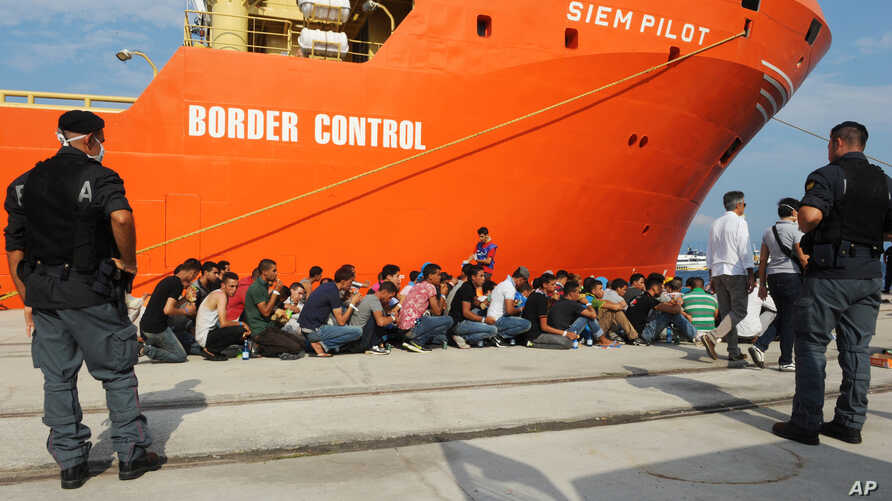 Rescued migrants line up after disembarking from the Norwegian cargo ship Siem Pilot at the Reggio Calabria's harbor, Italy, Aug. 8, 2015.