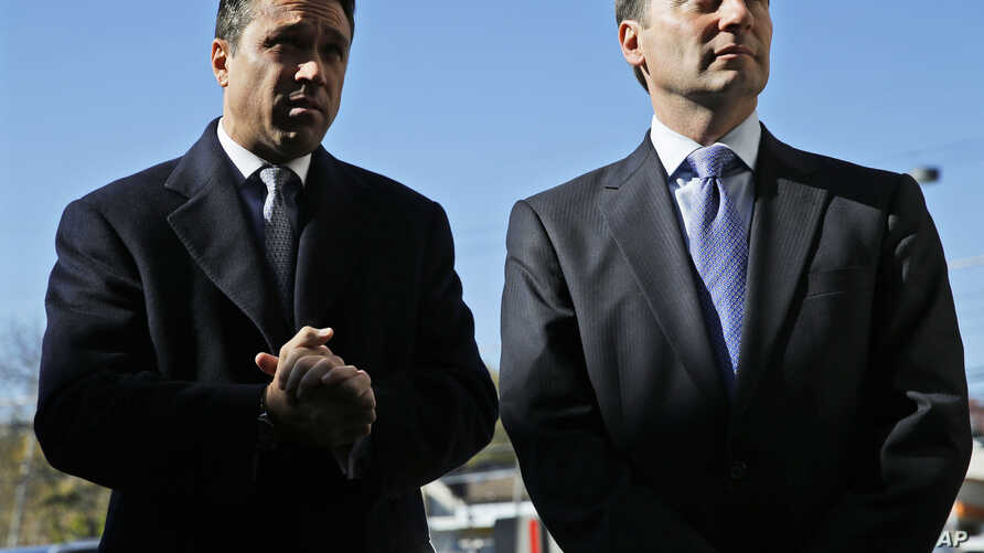 Republican gubernatorial candidate Rob Astorino (r) and Congressman Michael Grimm greet people as they exit a grocery store in the Staten Island borough of New York, Nov. 3, 2014.