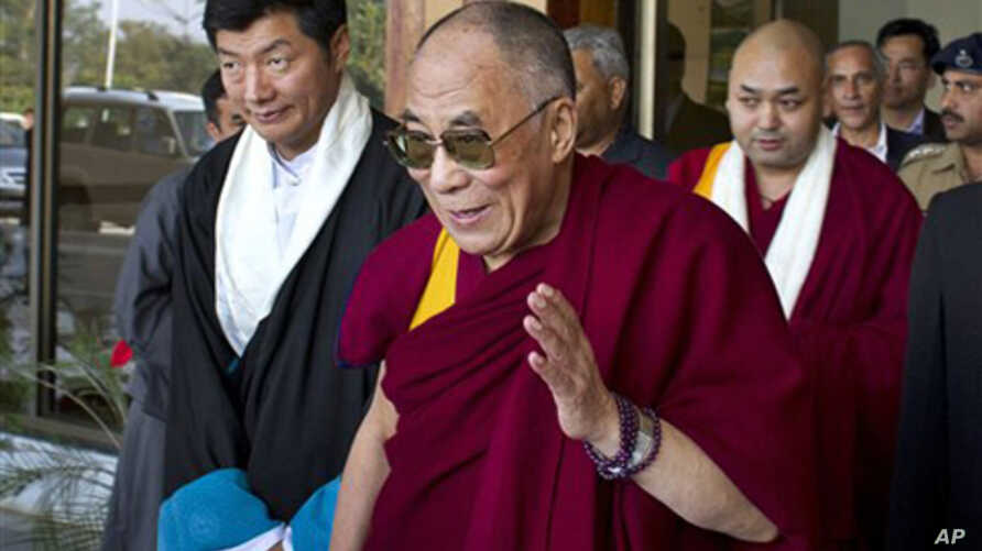 Tibetan spiritual leader the Dalai Lama, center, gestures after being received by the newly-elected Prime Minister of the Tibetan government-in-exile, Lobsang Sangay, left, as he arrives at the Kangra airport near Dharmsala, India, Sunday, Nov. 13, 2