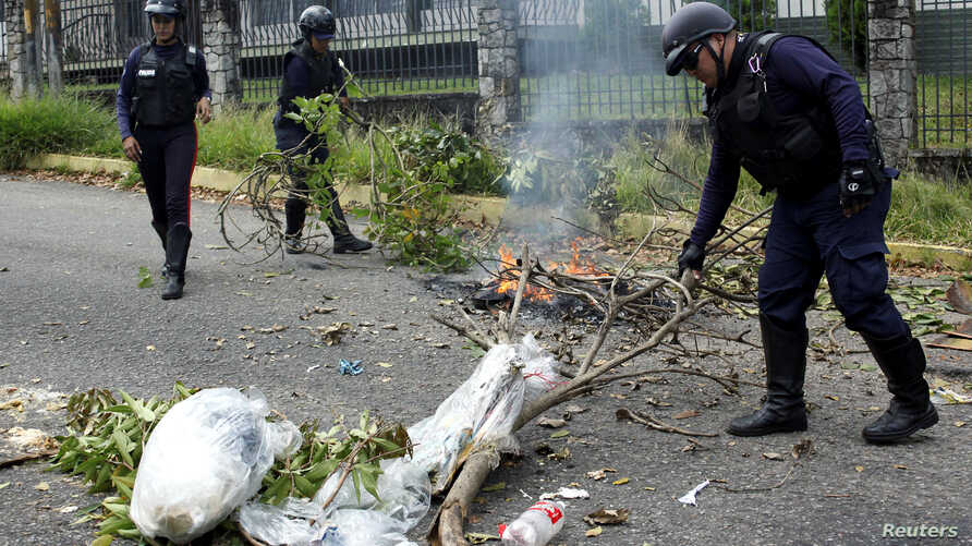 Police officers remove debris used by demonstrators to block a street during a protest against the gas shortage in San Cristobal, Venezuela, Sept. 21, 2018.