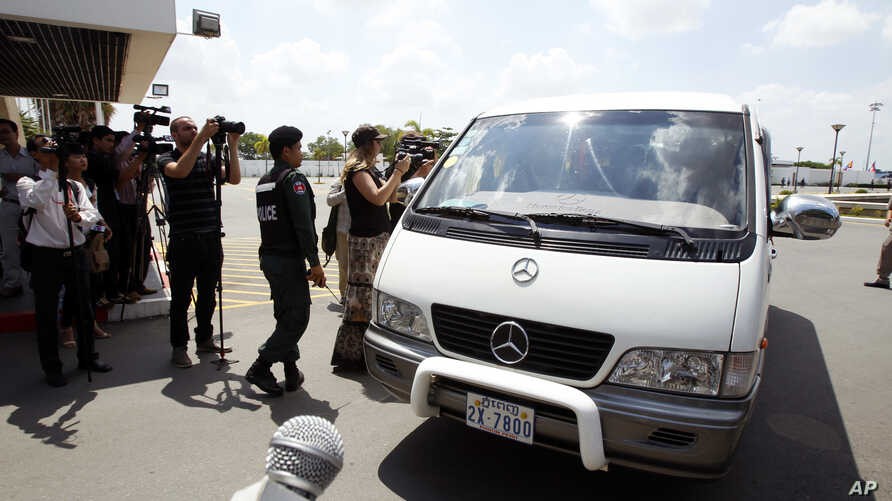 A van drives four refugees from Australia out of Phnom Penh International Airport, in Phnom Penh, Cambodia, Thursday, June 4, 2015.