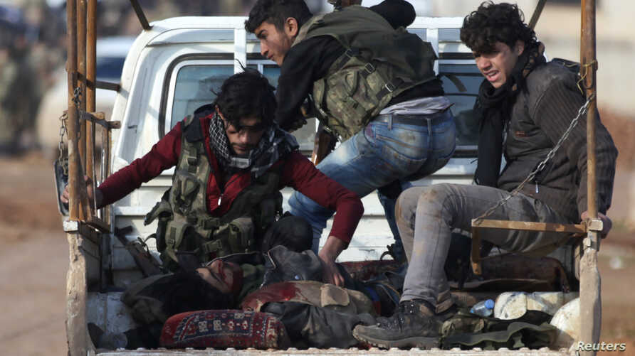 Free Syrian Army fighters ride on a pick-up truck with a fellow fighter, who was injured during an offensive, on the outskirts of the northern Syrian town of al-Bab, Jan. 10, 2017.