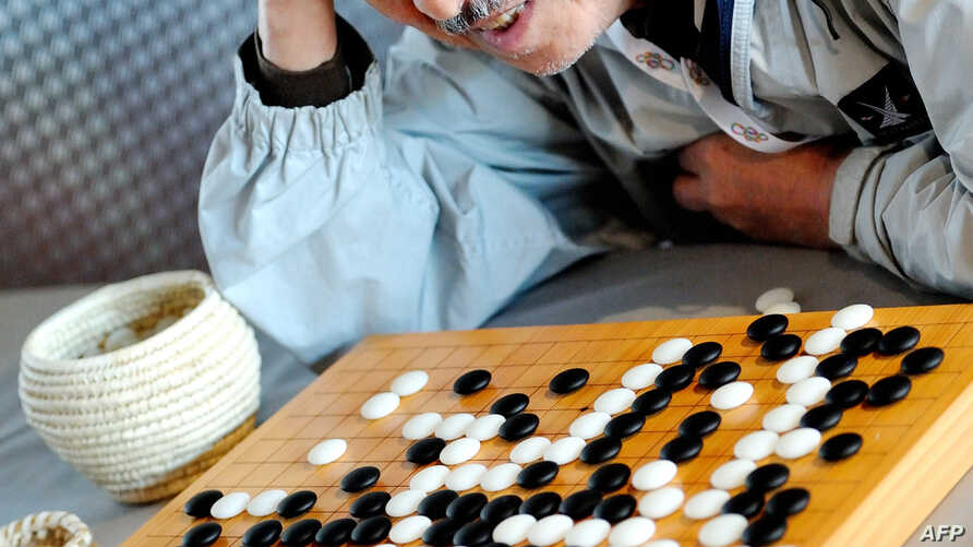 FILE - A man plays Go at the Grand Palais in Lille, northern France, Aug. 10, 2012. For the first time, a computer defeated a professional human being in a Go game.