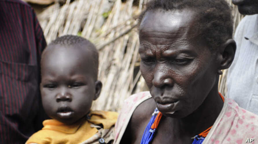 A mother waits with her son, both victims of ethnic violence in Jonglei state, South Sudan, for emergency food rations in the town of Gumuruk, Jan.12, 2012.