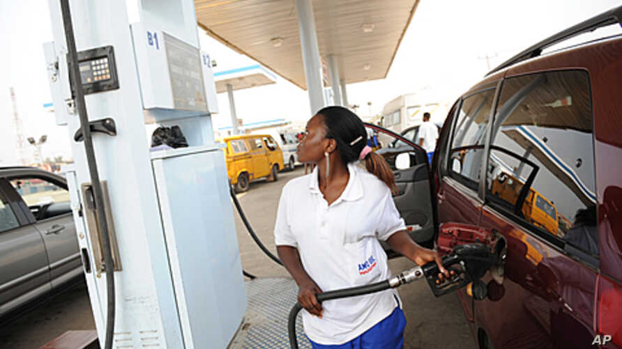 A  fuel attendant fills a tank at a gas station on Lagos' Ibadan highway where new pump prices were implemented. Queues formed at gas stations, protests broke out and unions threatened to paralyze Nigeria over a deeply controversial measure that has