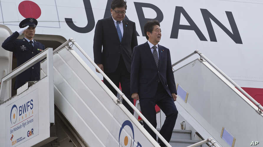 Japanese Prime Minister Shinzo Abe, right, gets down from the plane as he arrives in New Delhi, India, Dec. 11, 2015. Abe is on a three-day visit to India.