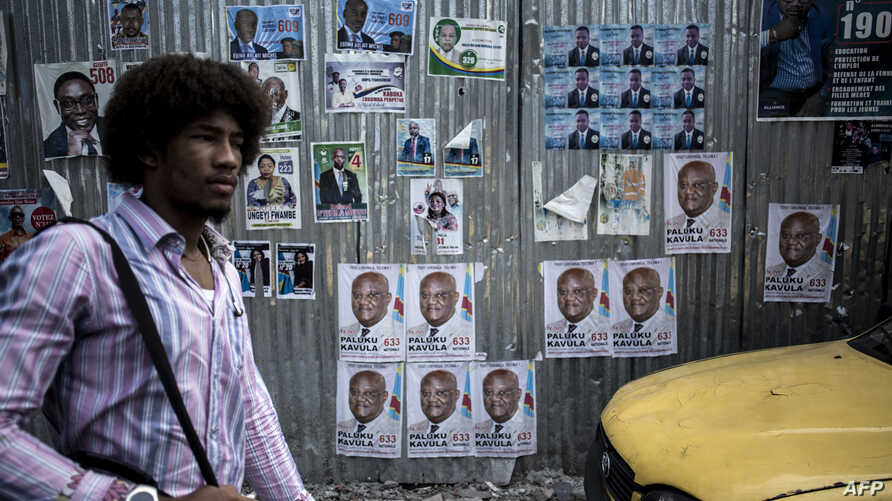 A man walks past a wall filled with campaign posters in the district of Lingwala in Kinshasa, Dec. 18, 2018.