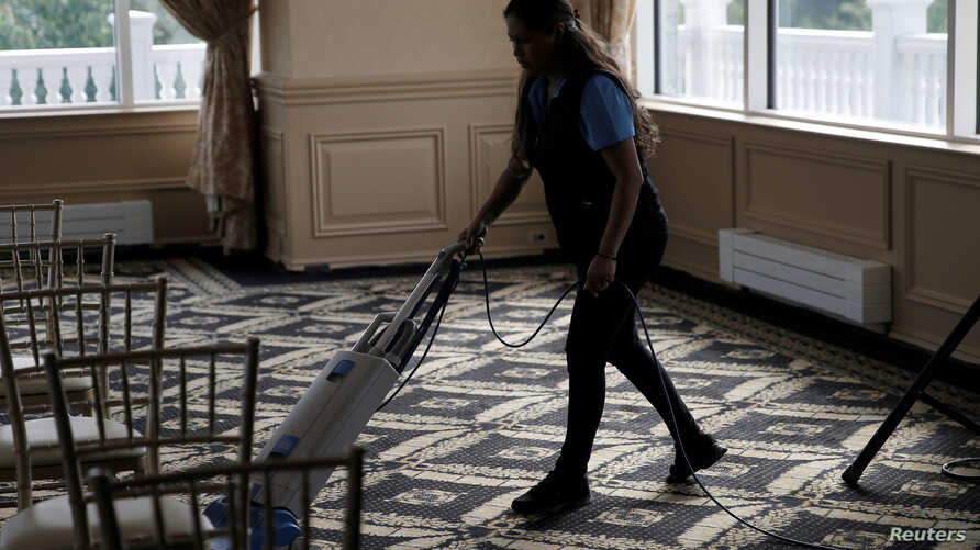 FILE - An employee vacuums the floor inside the clubhouse of the Trump National Golf Club Westchester, in Briarcliff Manor, N.Y., June 7, 2016.