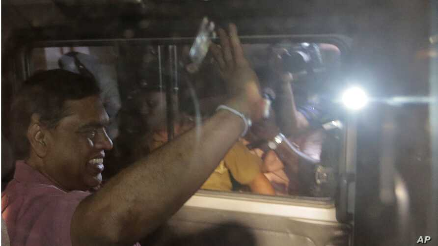 FILE - Sri Lanka's former Economic Affairs Minister Basil Rajapaksa waves to media from inside a police vehicle as he is taken to be produced before a judge in Colombo, Sri Lanka, April 22, 2015.