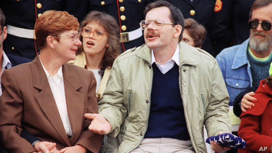 FILE - Terry Anderson holds an American flag presented to him while sitting with his sister Peggy Say during a ceremony in his honor at Dulles International Airport in Chantilly, Virginia, sponsored by No Greater Love, Dec. 12, 1991.