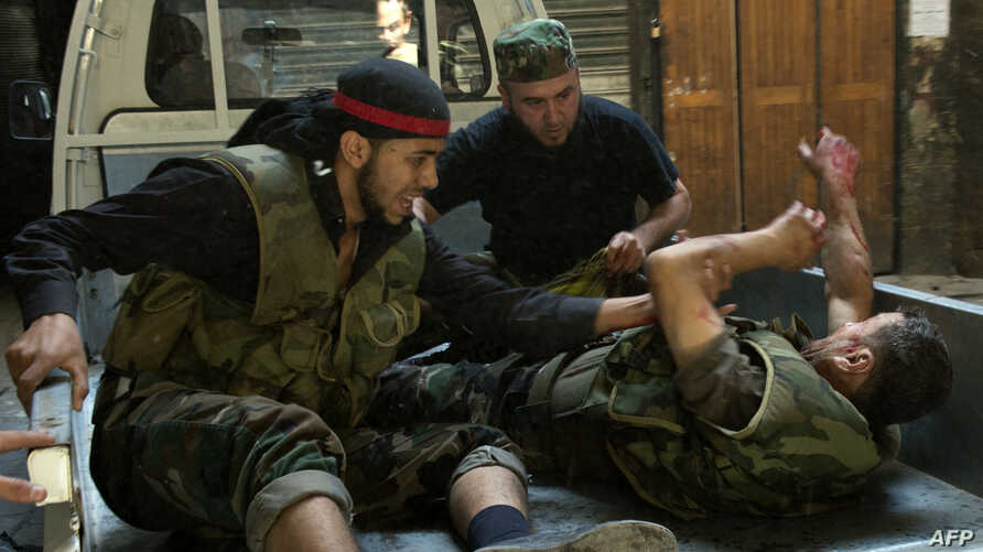 Syrian rebel fighters evacuate a wounded comrade during fighting with government troops in the old city of Aleppo, September 28, 2012.