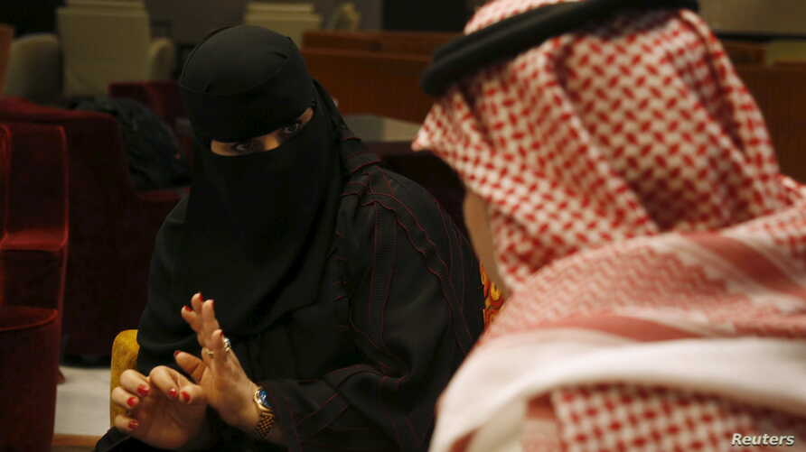 Saudi woman Fawzia al-Harbi, a candidate for local municipal council elections, gestures to one of her chaperones at a shopping mall in Riyadh November 29, 2015.