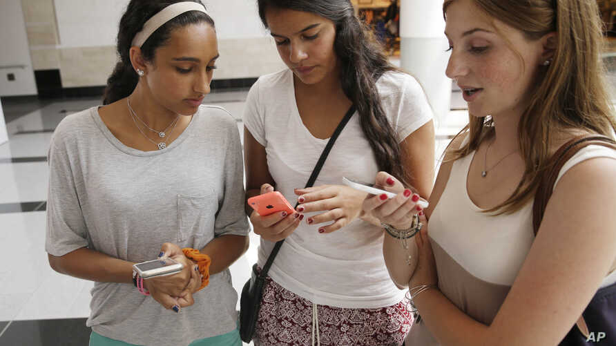 Isabella Cimato, 17, left, Arianna Schaden, 14, center, and Sofia Harrison, 15, check their phones at Roosevelt Field shopping mall in Garden City, N.Y.